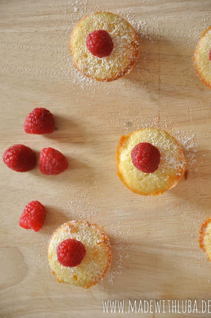Viele Mini Muffins mit Puderzucker und Himbeeren auf hölzernem Untergrund