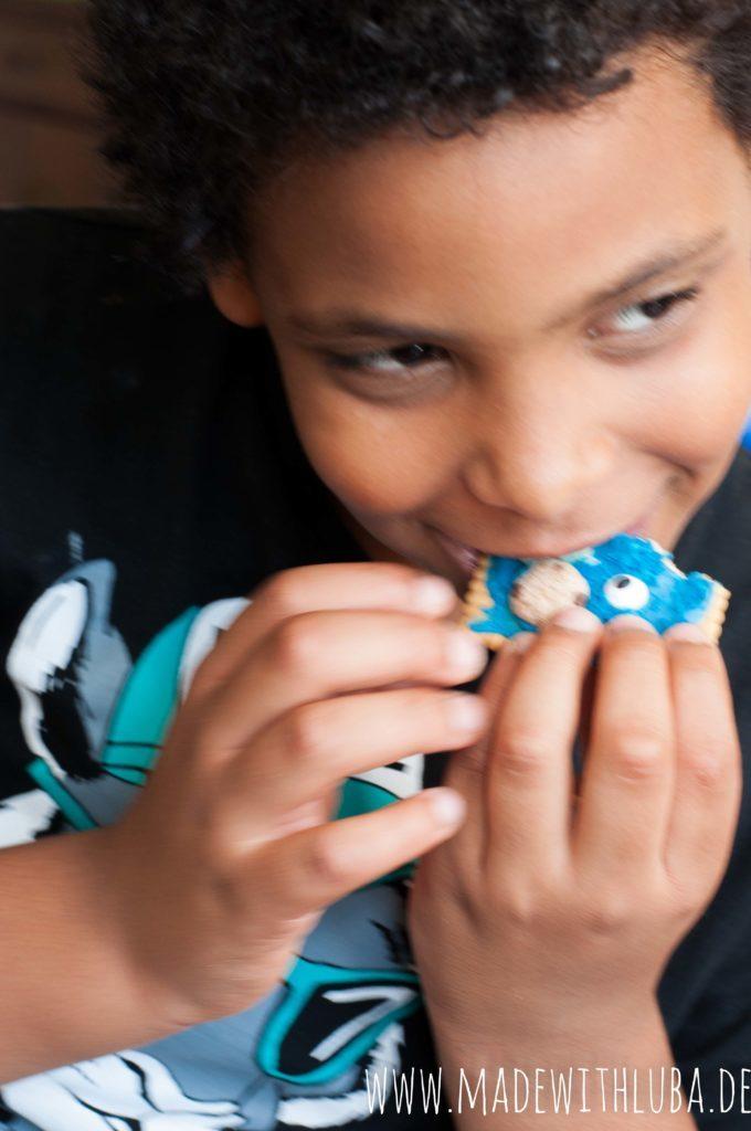 Junge der einen Krümelmonsterkeks isst
